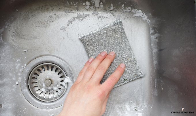 scrubbing a stainless steel sink with DIY cleaning product